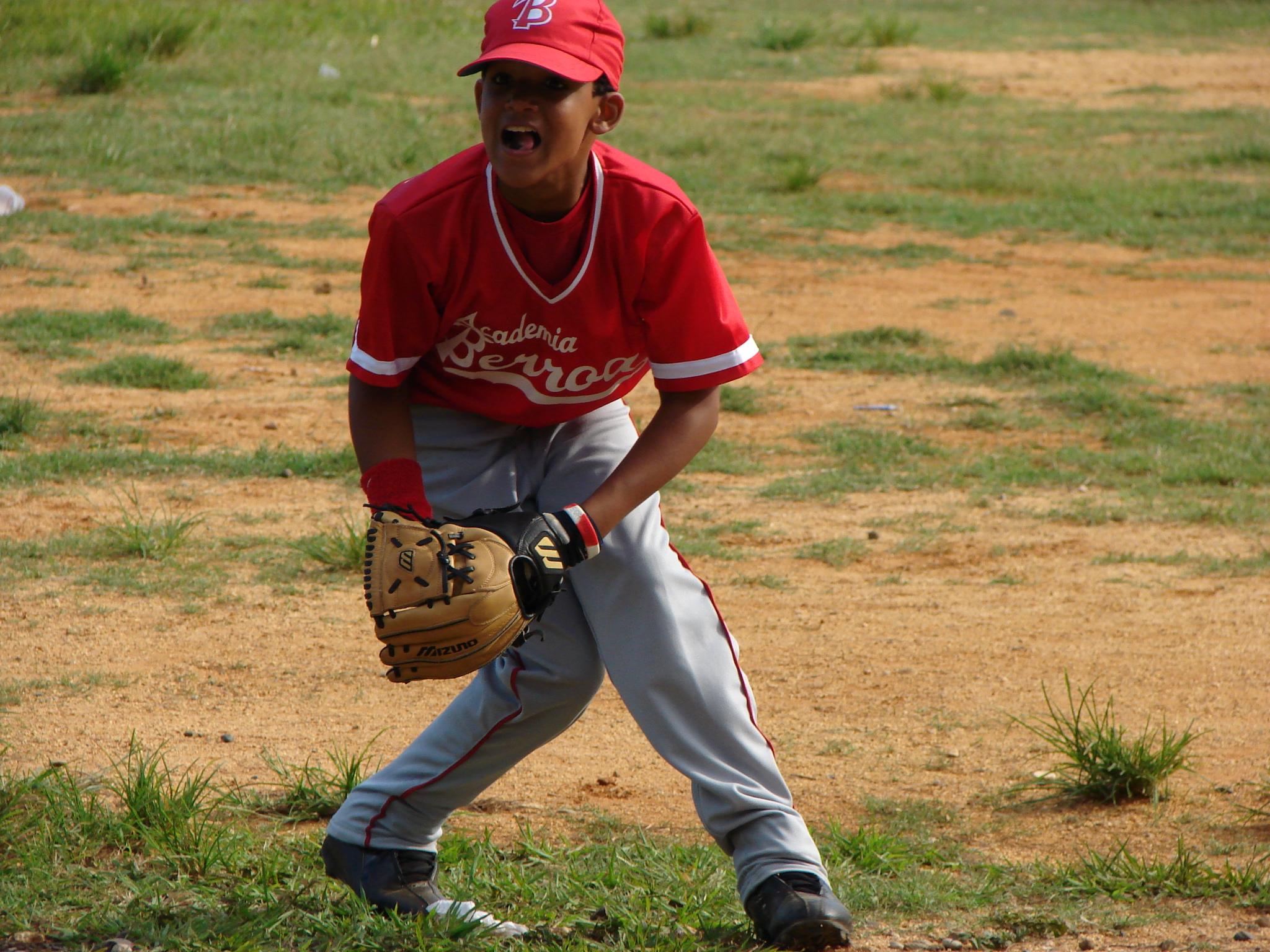 Baseball w Dominkanie, młodt gracz baseballa łapie piłkę